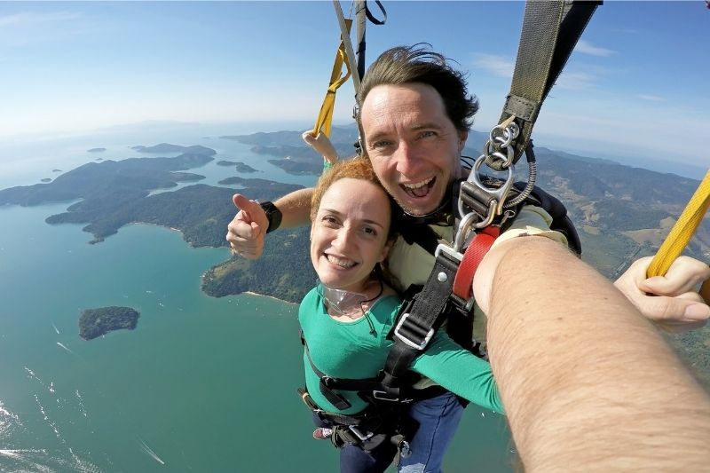 self portrait of a couple sky diving in tandem while in the air with parachute on