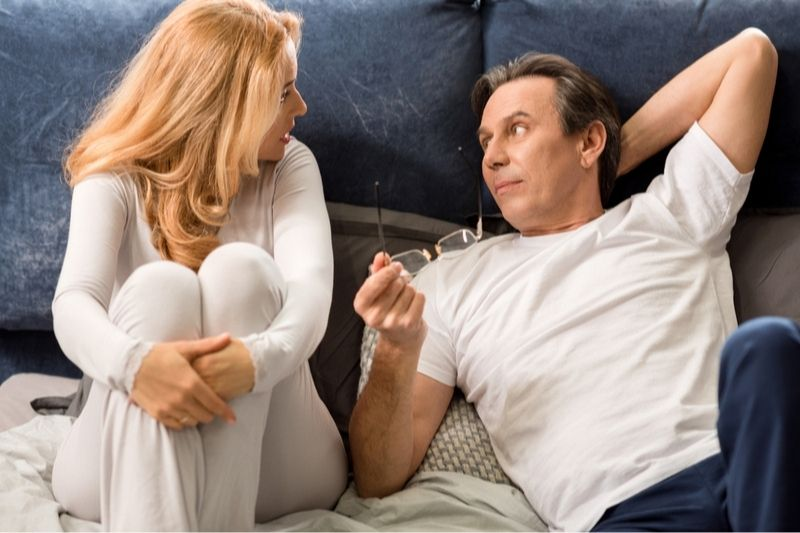 serious couple talking in bed with man lying holding an eyeglasses and woman sitting