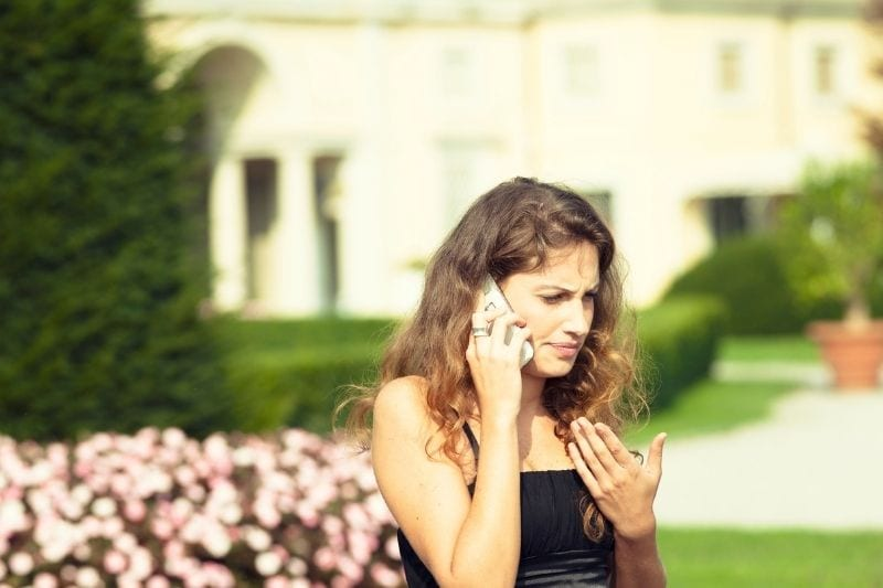 serious young woman calling outdoors in a public park