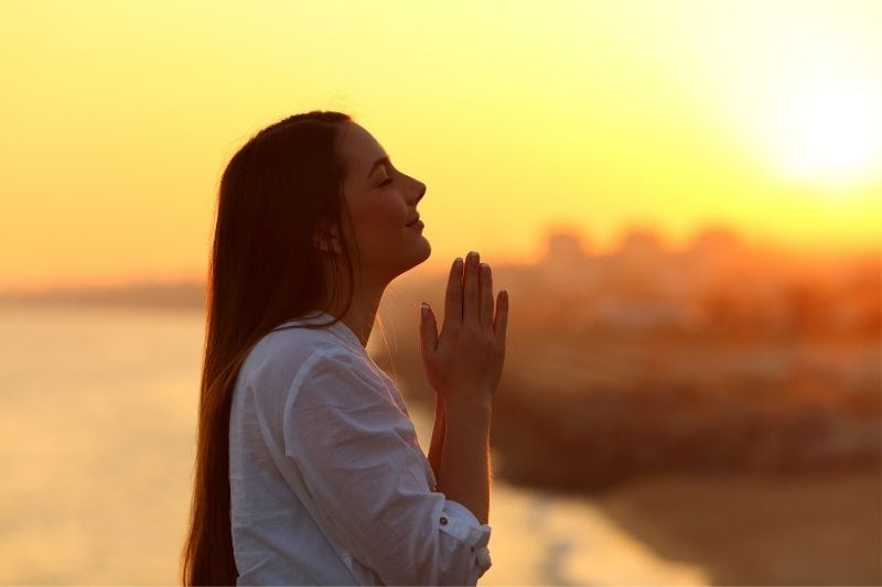 sideview of a praying woman with praying hands standing outdoors during golden hour