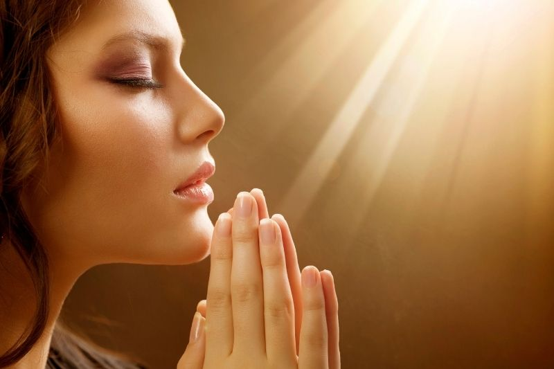 sidevoew of a pretty woman praying with hands close together with sun rays above