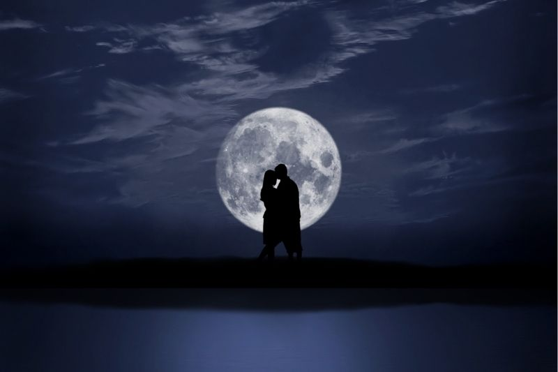 silhouette of a loving couple with a big moon behind them standing near a body of water