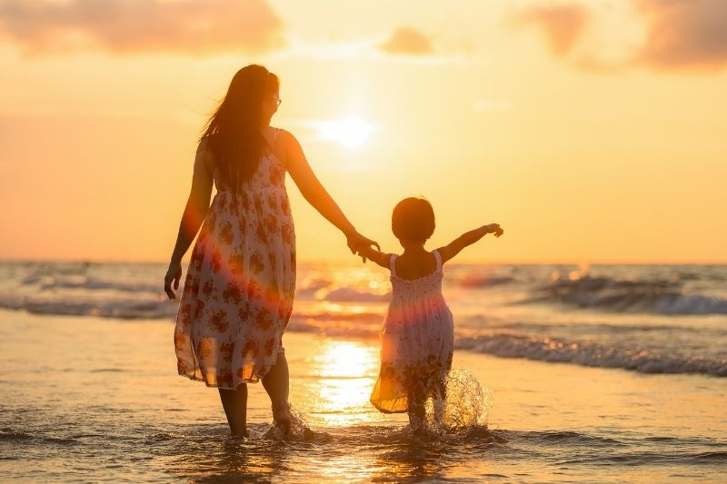 silhouette of a mother and daughter by the sea facing the sun set