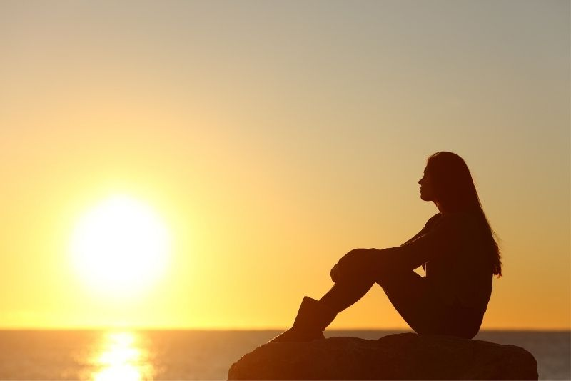 silhouette of a pensive woman sitting on rock in sideview viewing the setting sun above the sea