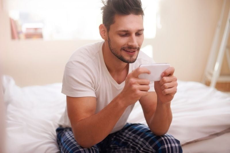 smiling man texting in bed wearing pajamas