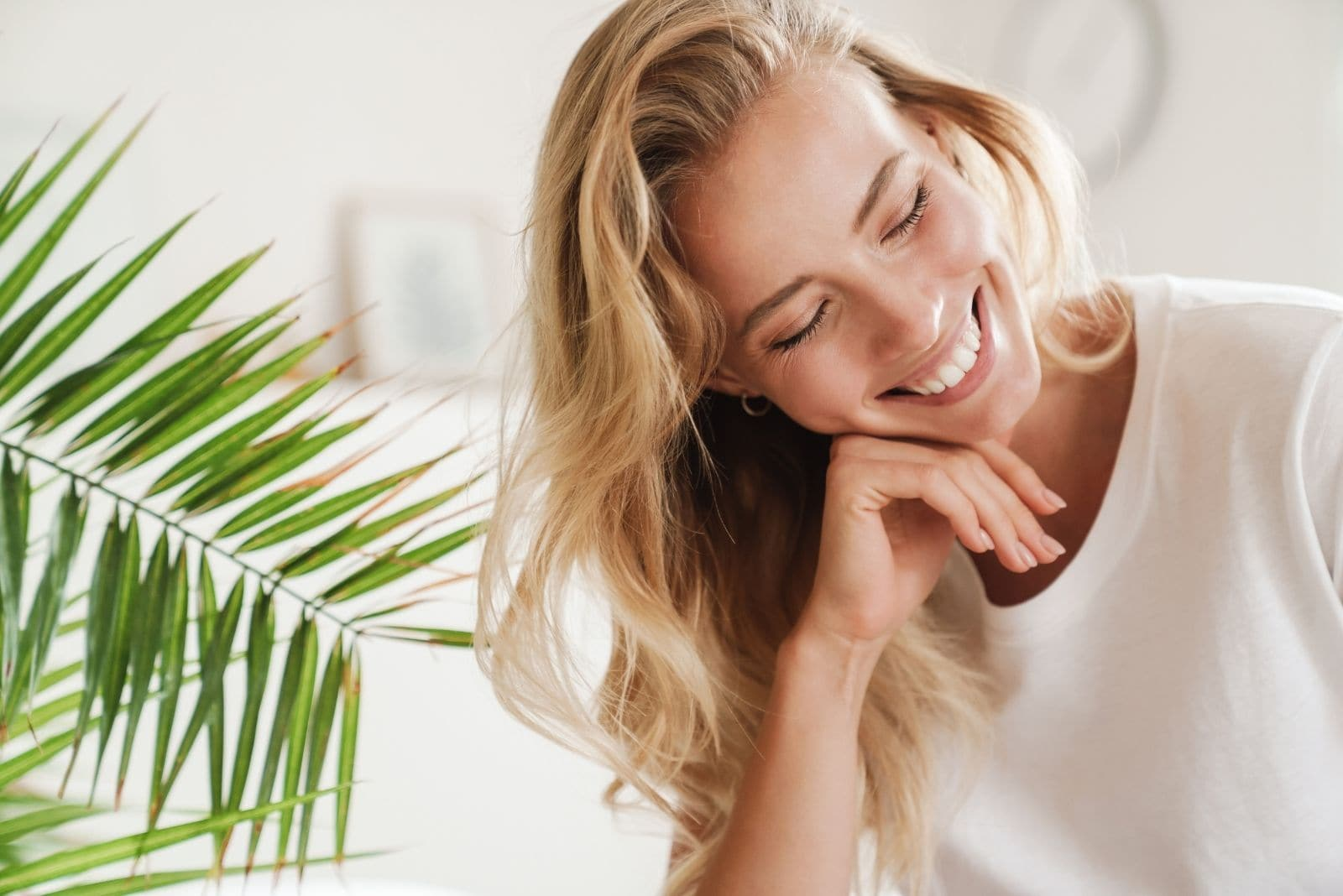 smiling woman closing her eyes sitting inside the living room with plant behind her