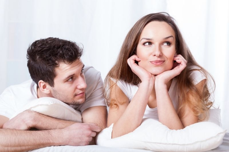 stubborn confident woman and a loving shy man lying in bed beside her