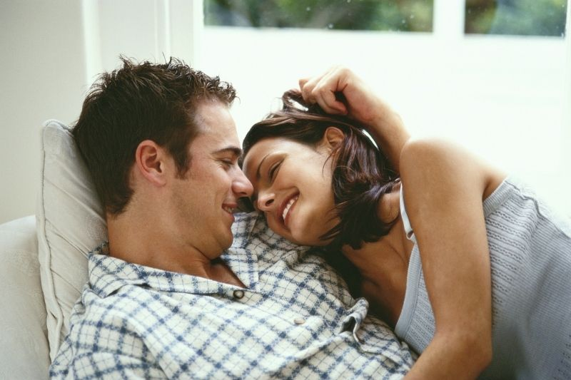 sweet couple cuddling and smiling inside home photo waist up