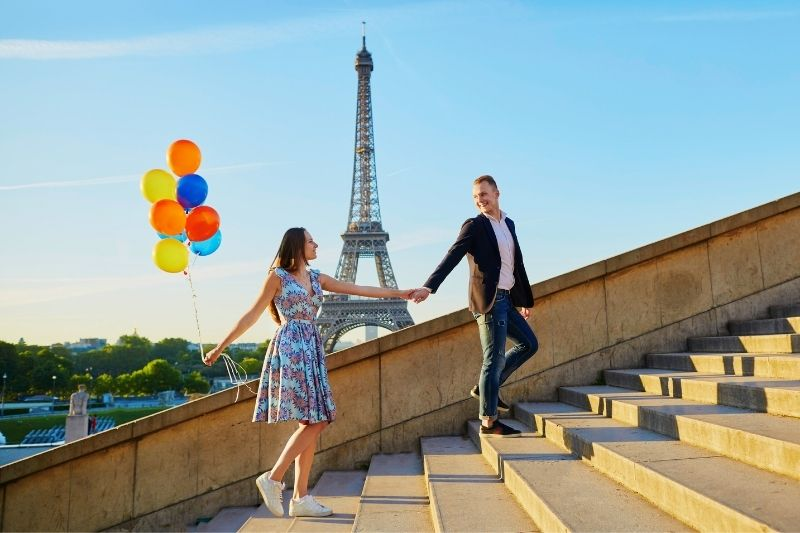 sweet couple hand in hand in the stairs with balloon near the eiffel tower in France