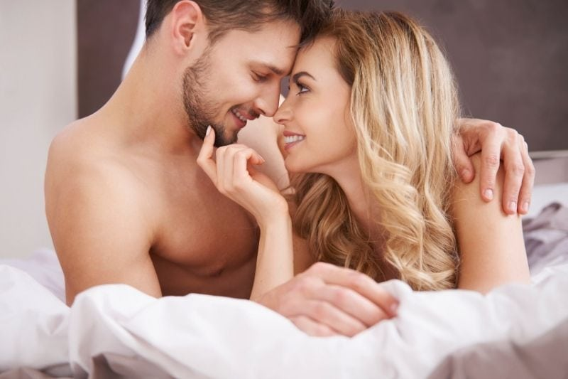 sweet romantic couple talking in bed shirtless cuddling in bed
