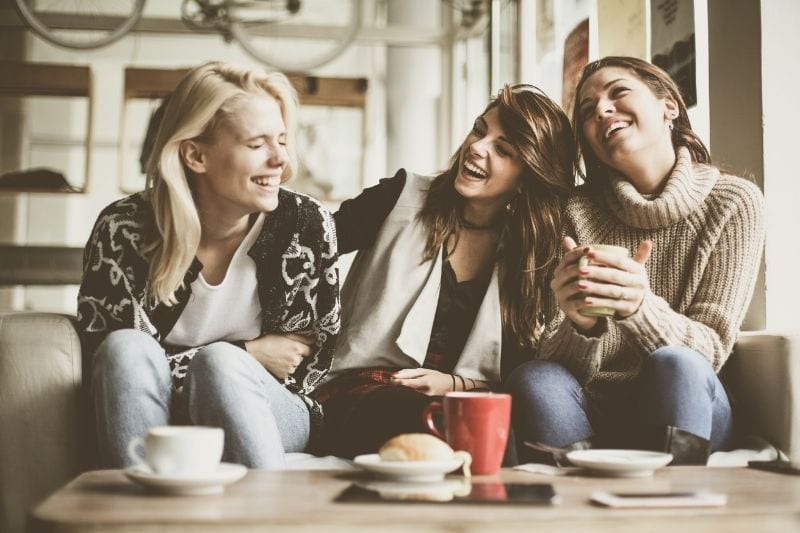 three friends laughing over coffee inside a cafe