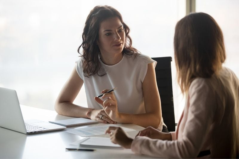 two diverse businesswoman discussing serious business inside office sitting by the office table