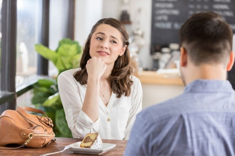 uneasy young woman in a first date with a man in a cafe