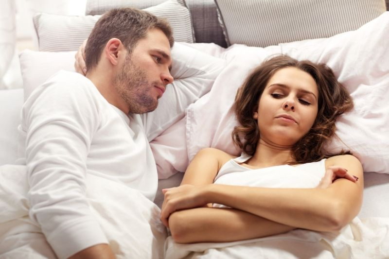 unhappy couple arguing in bed lying down with man facing the woman