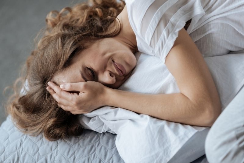 unhappy moody woman crying in bed while lying down holding her head