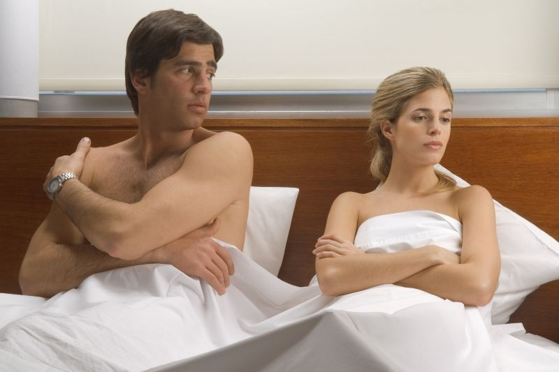 upset couple sitting in bed naked covered with white blanket while leaning in the pillows from headboard