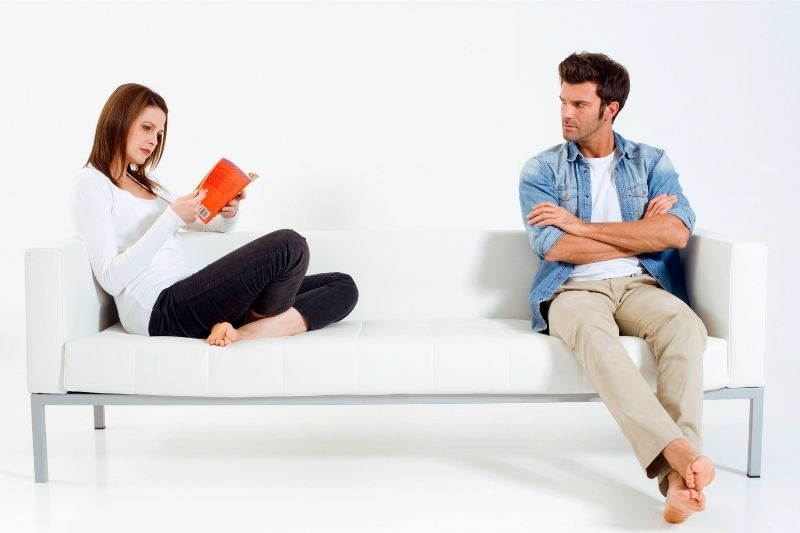 upset man sitting on the sofa with a woman reading a book at the opposit end of the sofa