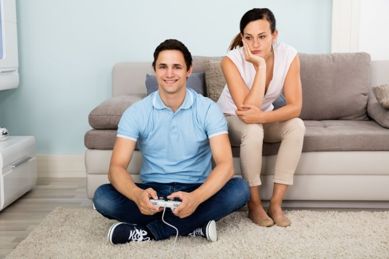 upset woman beside a busy man playing video games inside home