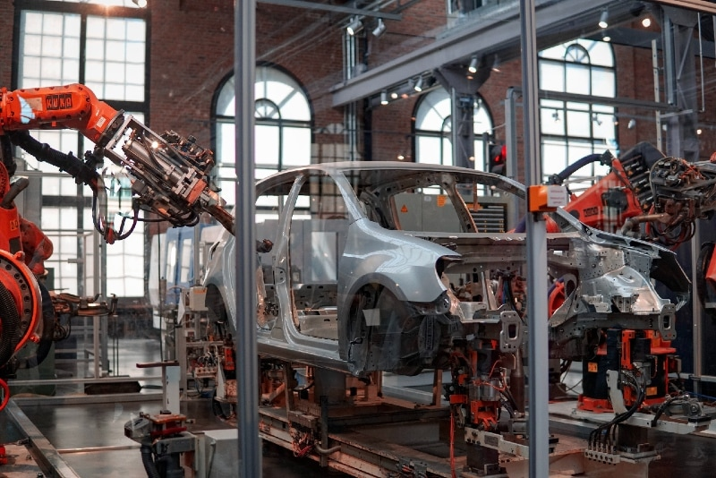 vehicle being fixed inside factory using robot machines
