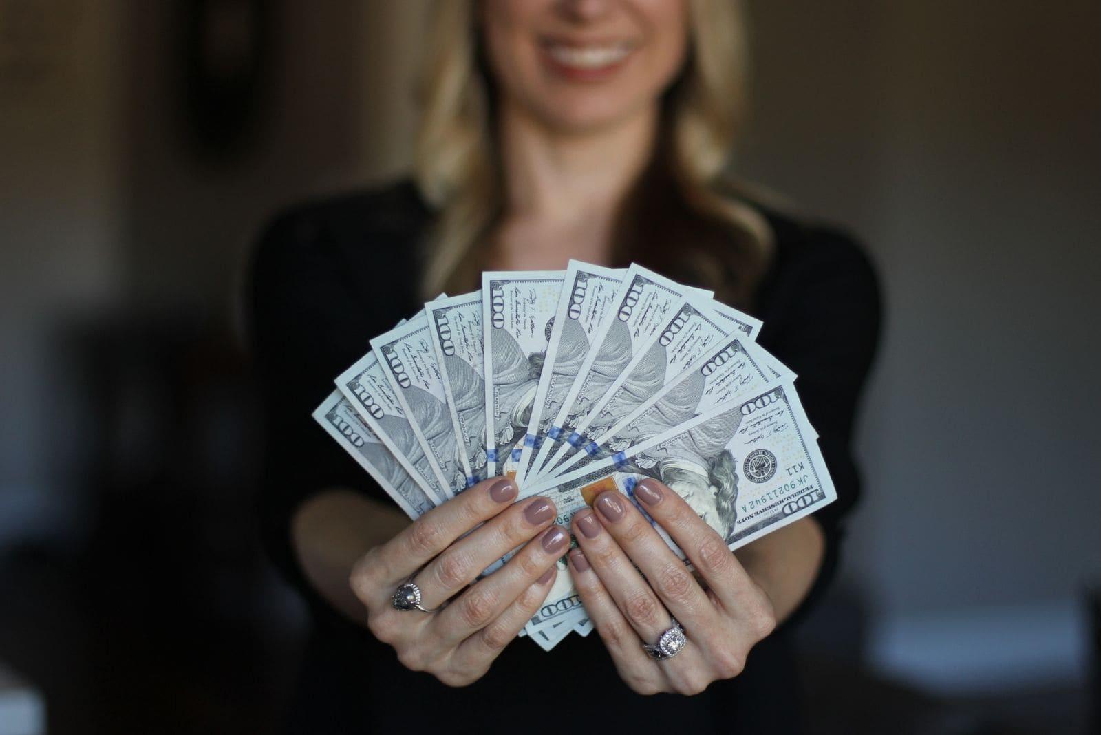wealthy woman showing money in her hands in focus