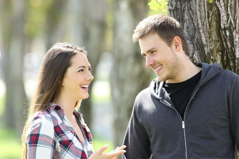 woman and man talking outdoors under a tree in the park
