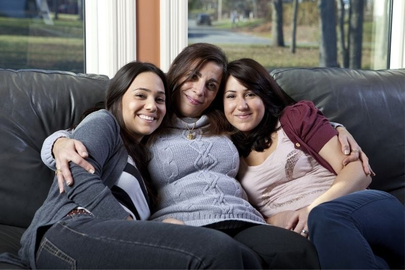 woman and two daughters sitting in the couch inside living room looking at the camera smiling