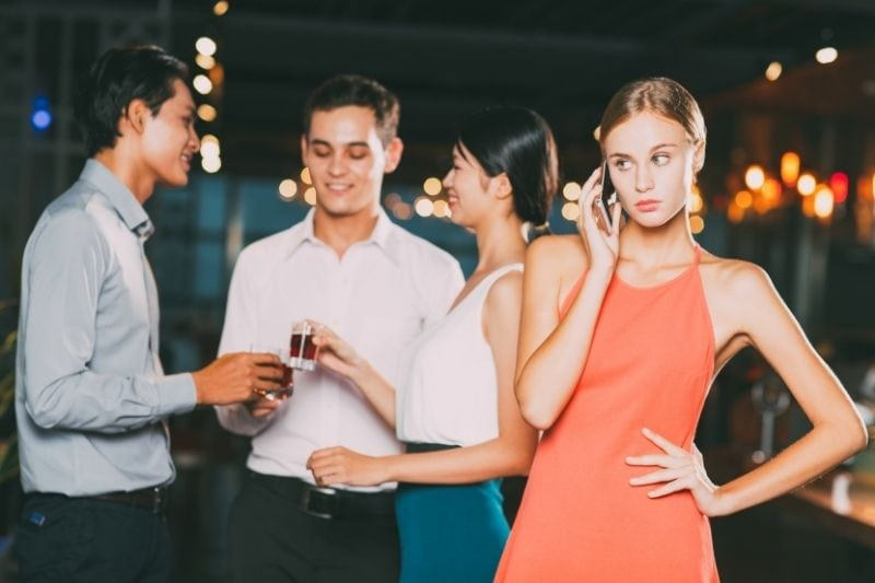 woman at party with friends answering phone looking pissed off
