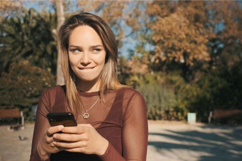 woman biting lip while texting and standing outdoors