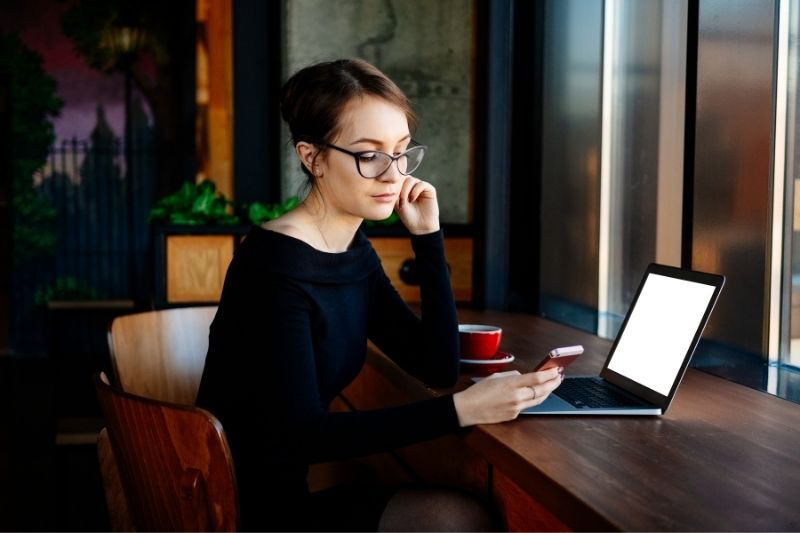 woman checking mobile phone while sitting at the table with laptop while working