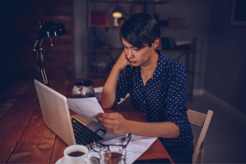 woman checking phone bill sitting at the table with laptop and coffee and lot of papers in the night