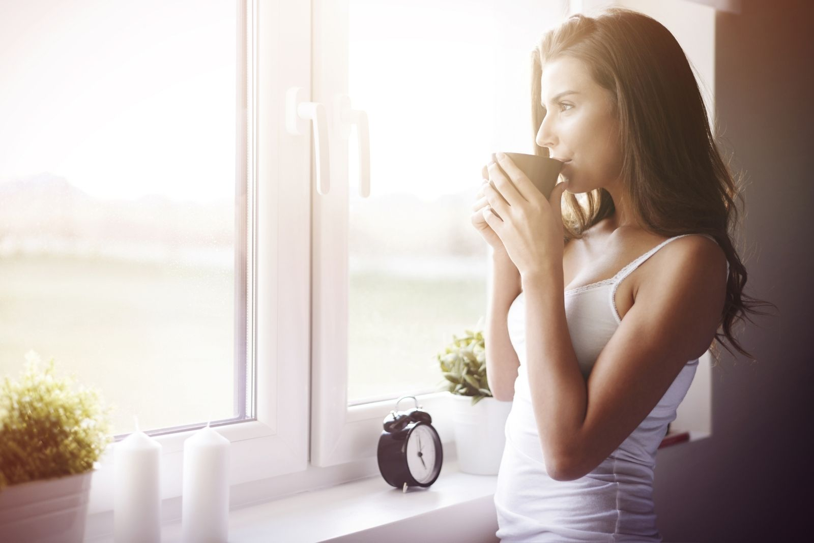 woman drinking coffee looking outside the window with an alarm clock nearby
