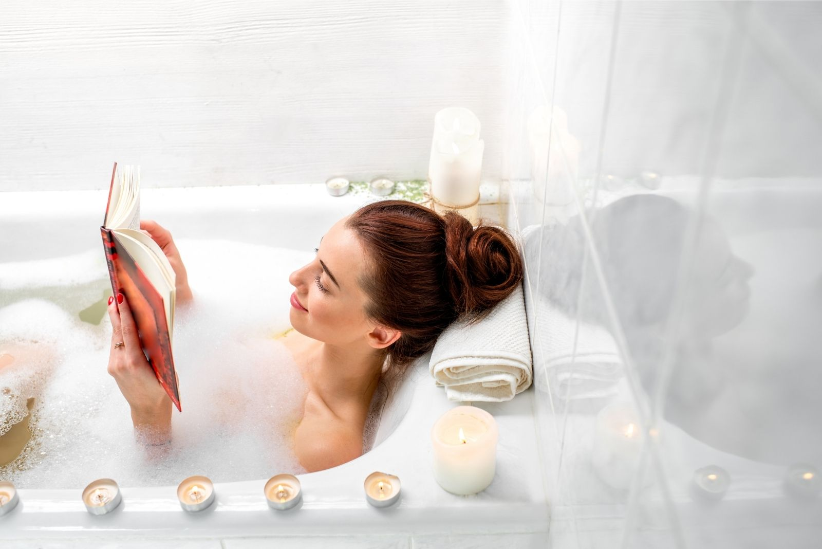 woman enjoyed bathing in the tub with lighted candles around while reading a book