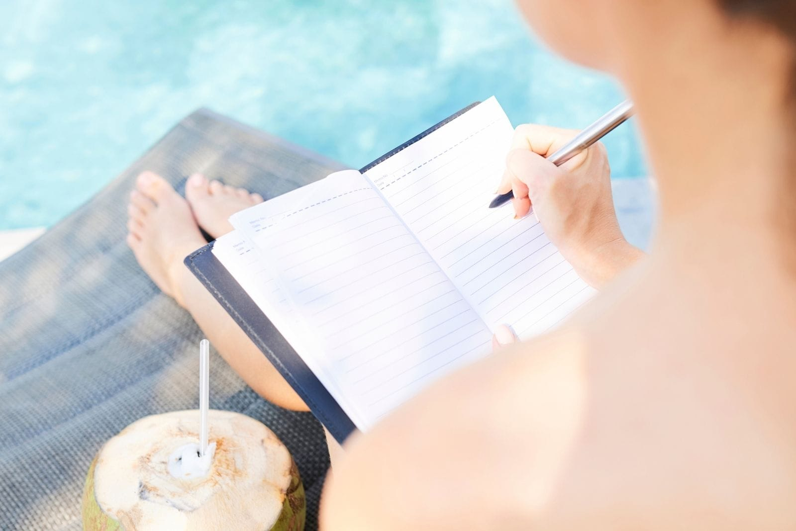 woman filling gratitude journal at the poolside with a coconut drink beside her