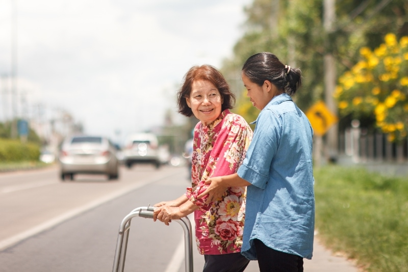 woman helping woman with walker crossing the street