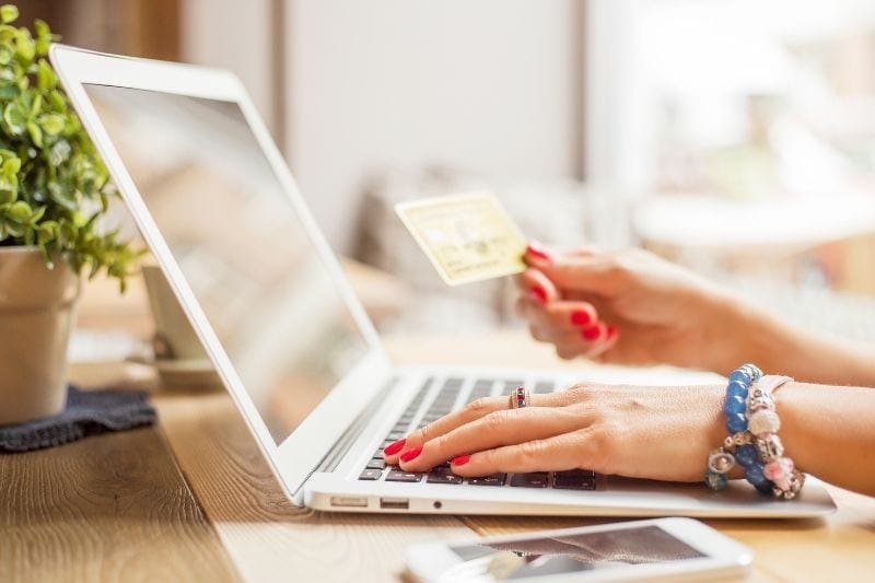 woman holding an atm card while browsing the internet in her laptop