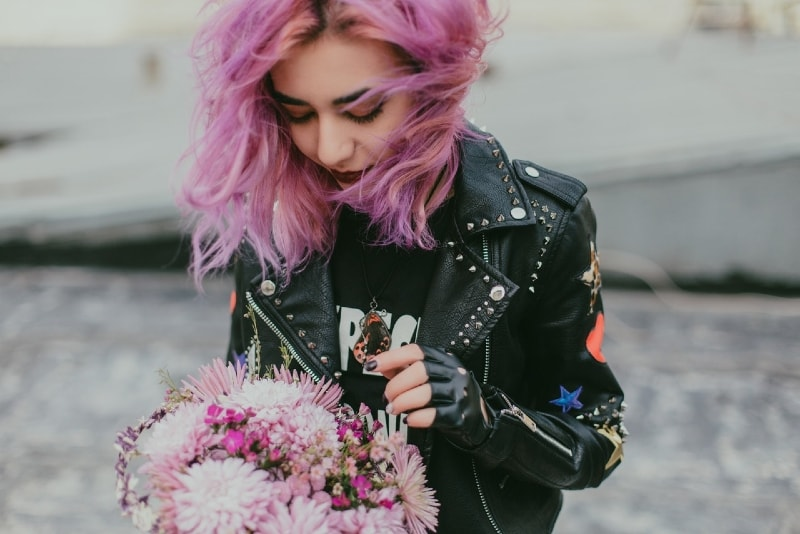 woman with pink hair holding bouquet of flowers
