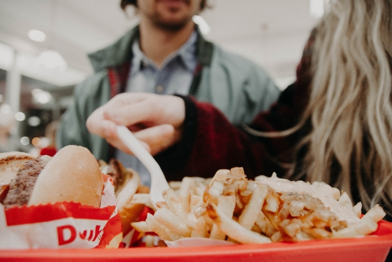 blonde woman in red coat holding fork over fries