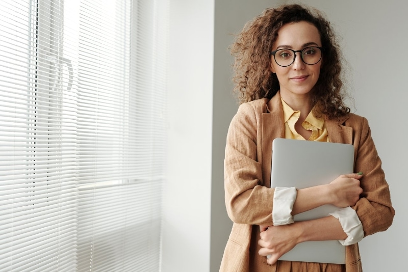 woman with eyeglasses holding silver laptop