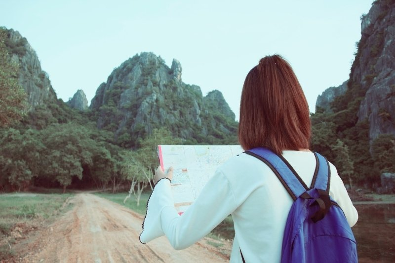woman with blue backpack holding map