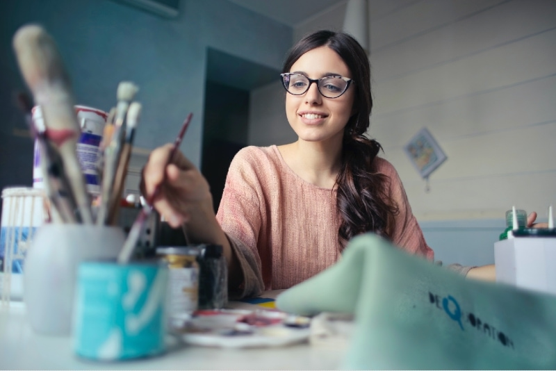 happy woman with eyeglasses holding paint brush