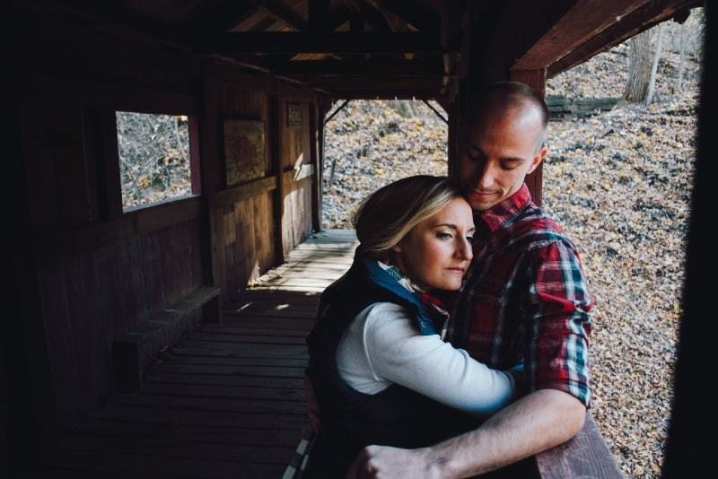 blonde woman hugging man in checked shirt during daytime