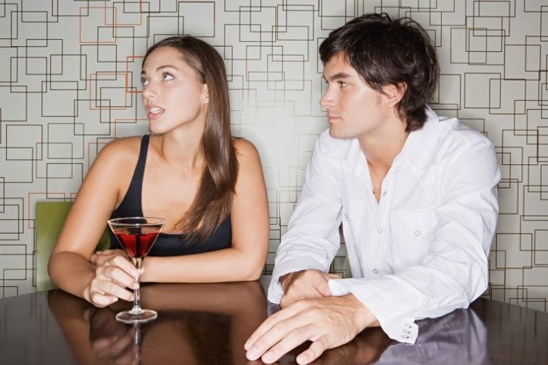 woman ignoring the man during their date in a bar