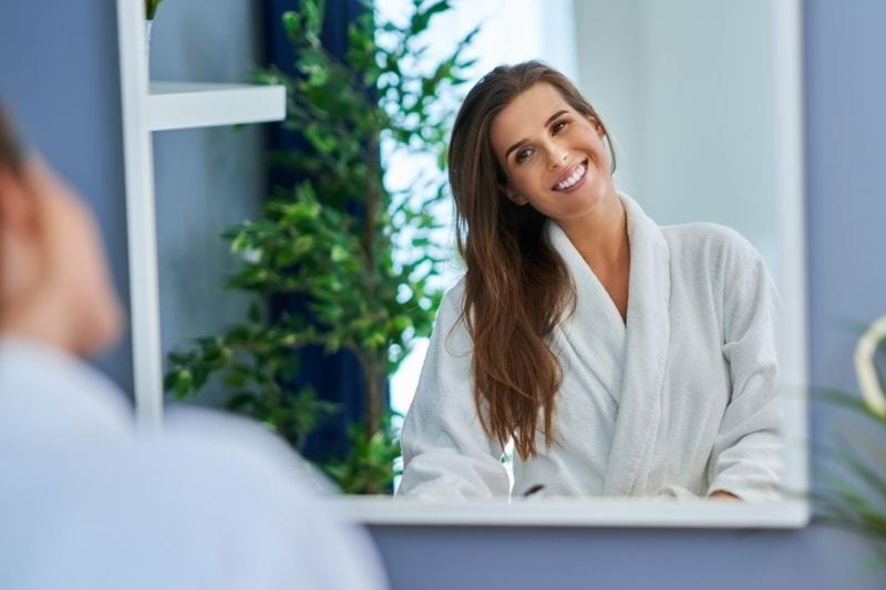 woman in bath robe smiling in front of a mirror
