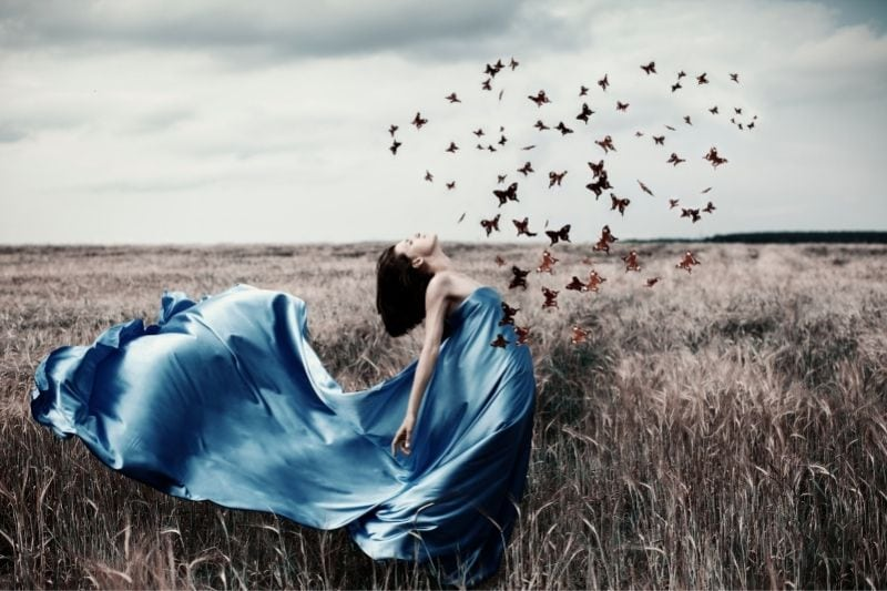 woman in blue satin lace in the midlle of the field with butterflies flying forming heart shape