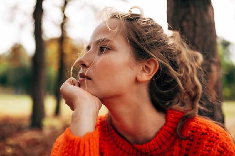 woman in orange sweater thinking deeply while sitting outdoors