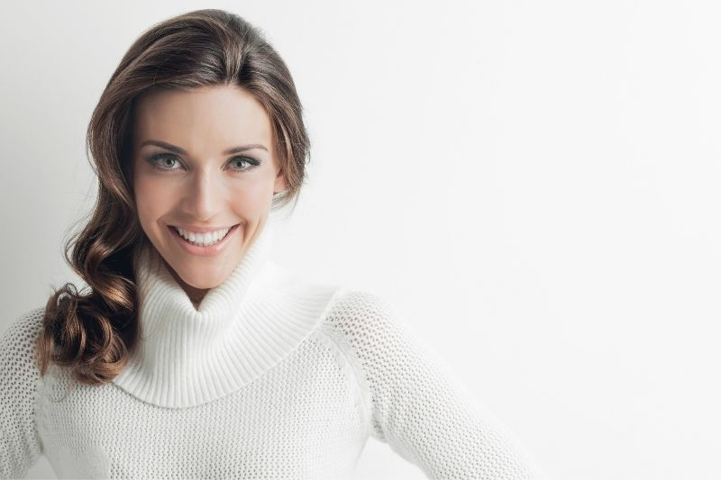 woman in sweater smiling and standing near white wall
