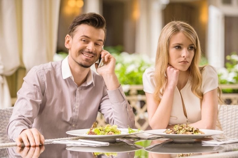 woman is getting bored with her boyfriend always on the phone during their date