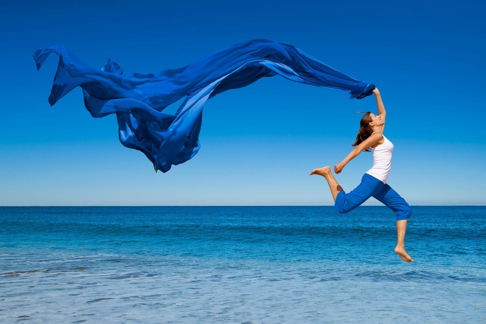 woman jump with joy near the blue sea carrying a blue cloth blown by the wind