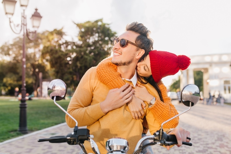 woman kissing man's neck while sitting on scooter
