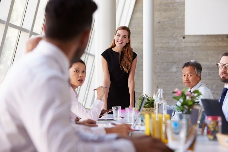 woman leading a meeting standing inside the meeting room with her colleagues lsitening